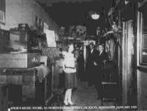 Henry Spier, standing on the right, in his music store.