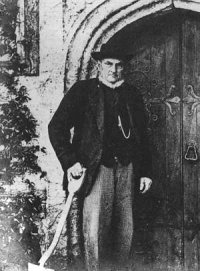 Photo of Turner by Warnham church door - holding his spade, despite being in his best clothes.