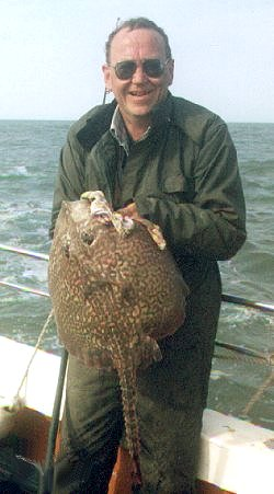 Keith Summers (pictured with the biggest fish he ever caught: a 17½ pound skate.  Photo by John Howson, I think) off Felixstowe, 1997.
